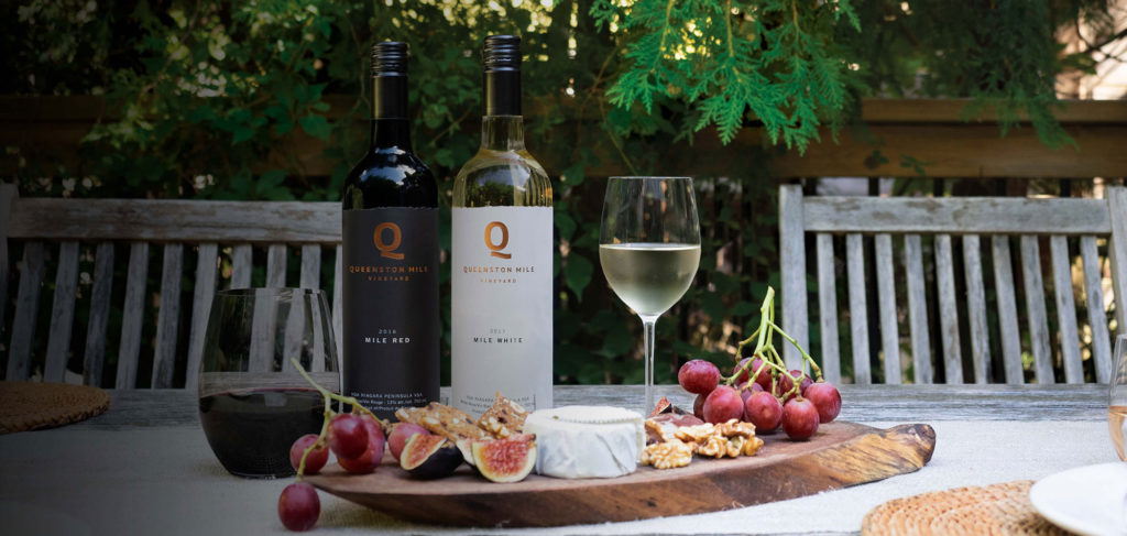queenston mile red and white bottles behind charcuterie boards
