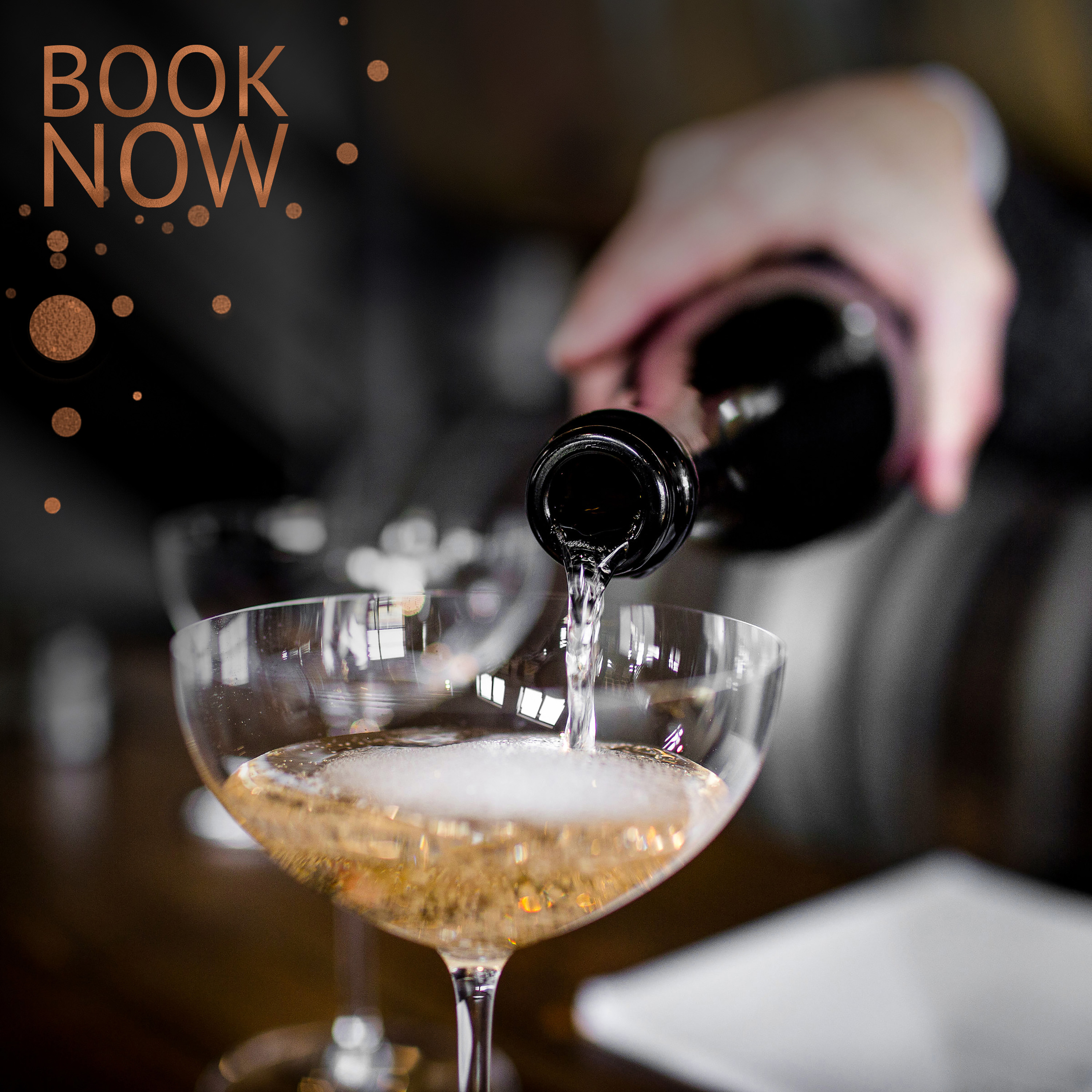 sparkling wine pouring into a coupe with words book now